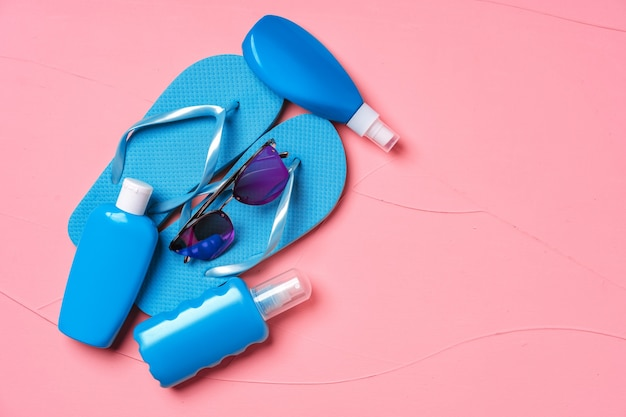 Blue flip-flops with sunscreen and sunglasses on pink, flat lay