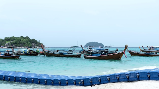 The blue floating dock is made of hdpe plastic on the beautiful blue sea. there are boats and mountains as a backdrop.