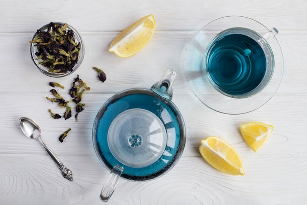 Blue flower tea in the glass teapot and cup on  the white wooden background. top view.