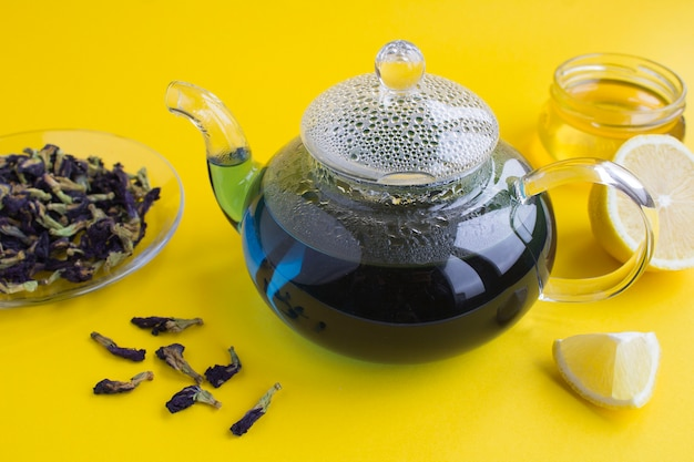 Blue flower tea in the glass teapot on yellow