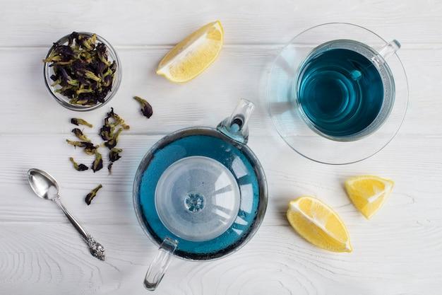白い木製の背景にガラスのティーポットとカップの青い花のお茶。上面図。