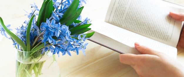 Синие цветы в вазе на переднем плане открытая книга в расфокусировке