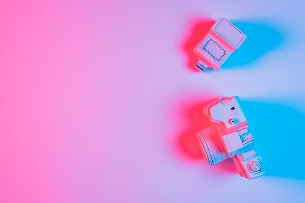 Luce blu del fuoco sulla macchina fotografica e sulla lente dipinte sopra fondo normale