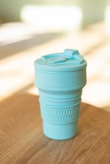 プラスチックなしのドリンク用の青い折りたたみ式シリコンカップ。インテリア内部の廃棄物ゼロのスタイルで、クローズアップ。