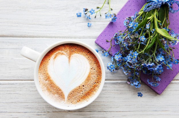 Голубые незабудки, блокнот и чашка горячего кофе.