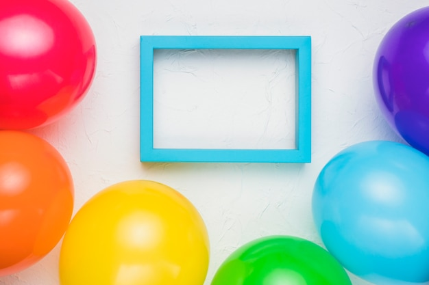 Blue frame and colorful balloons on white surface