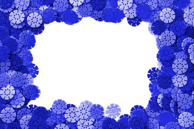 Blue frame designer background. multi-colored details in the form of snowflakes from the children's designer on white background. plastic discs for the development of fine motor skills of fingers.