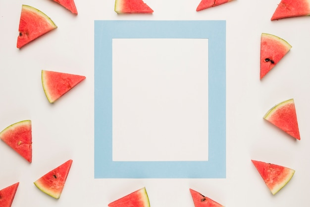 Blue frame and sliced juicy water melon on white surface