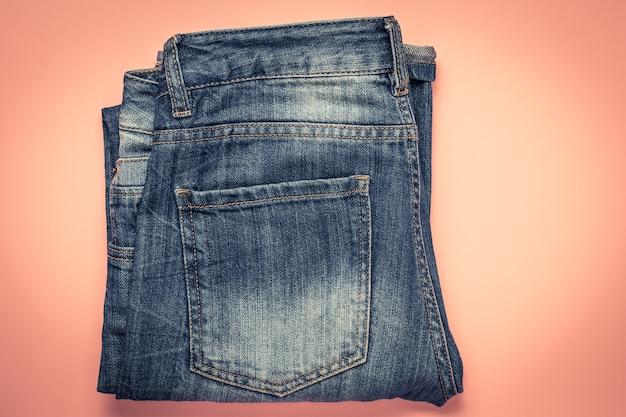 ポケット付きの青い擦り切れたジーンズ、ピンクの背景に折りたたまれたぼろぼろのパンツ。ダークデニム。