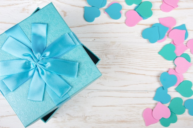 Blue gift box and paper hearts of pastel colors