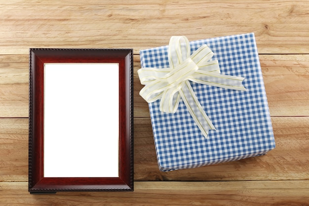 Blue gift box place near brown wooden frame