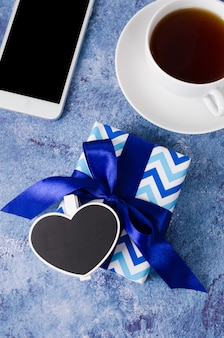 Blue gift box, smartphone and cup of tea on blue background.