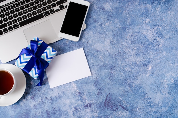 Blue gift box, smartphone with black blank screen on office desk, laptop and cup of tea on blue background.