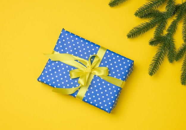 Blue gift box tied with ribbon on a gray background, top view. festive backdrop