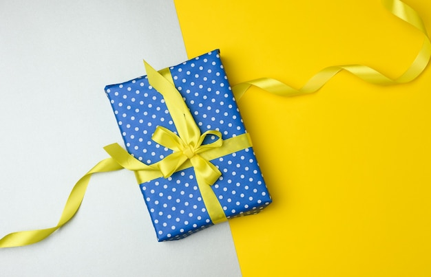 Blue gift box tied with a yellown silk ribbon on the gray background, top view. festive backdrop