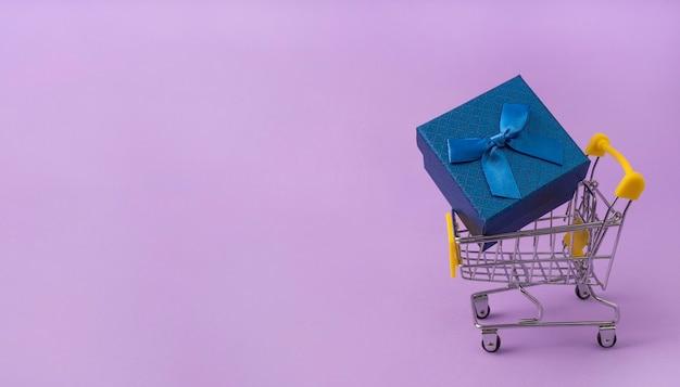 Синяя подарочная коробка с бантом в тележке супермаркета на сиреневом фоне