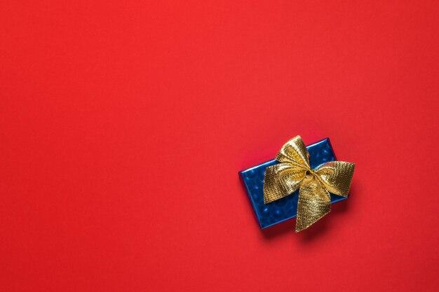 Синяя подарочная коробка с золотым бантом на красном фоне. подарок-сюрприз.