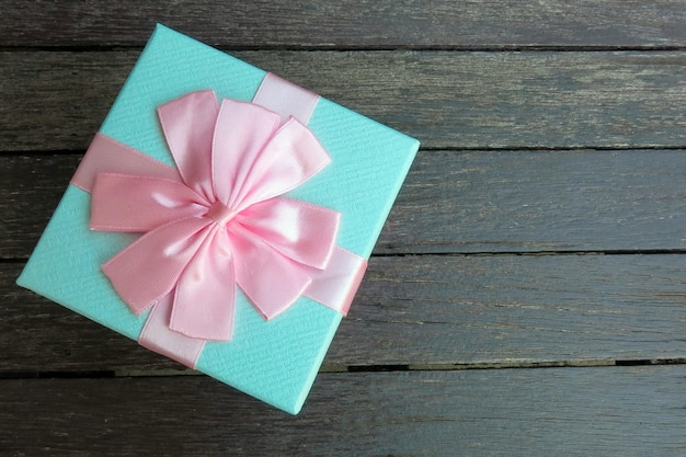 A blue gift box with pink ribbon on the black wooden background