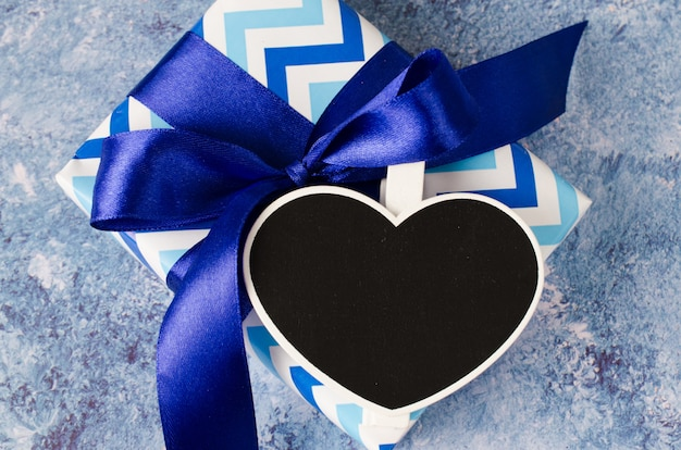 Blue gift box with ribbon. heart shaped chalkboard with copy space.