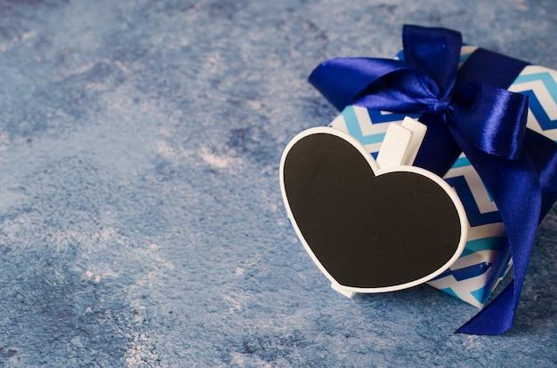 リボン付きの青いギフトボックス。ハート形の黒板コピースペース付き。