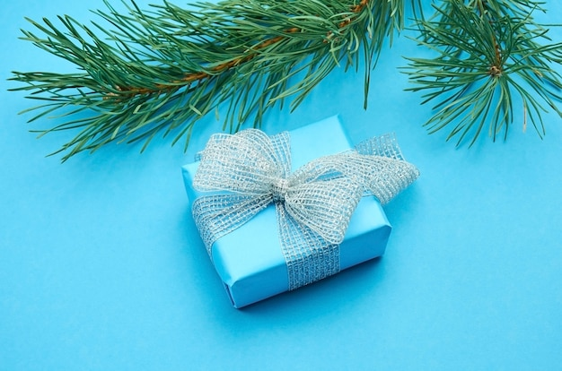 Blue gift box with silver bow and green pine tree branch