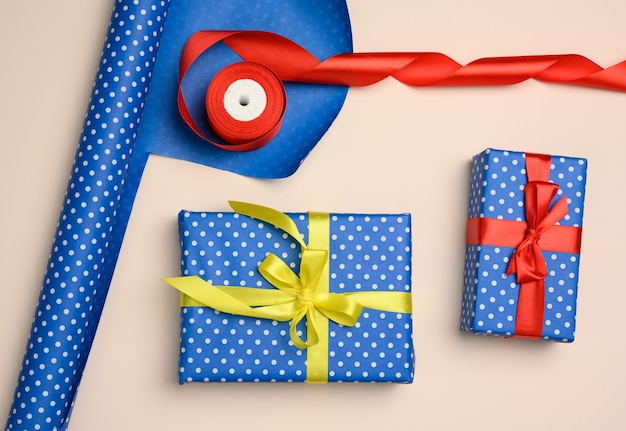 Blue gift box wrapped in silk ribbon on a beige background, top view