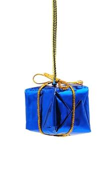 孤立した白い背景の上の青いギフトのクリスマスのおもちゃ。
