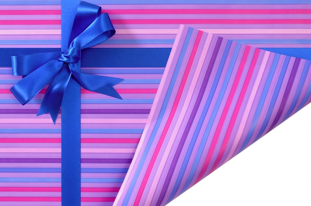 キャンディストライプ包装紙に青いギフトリボン弓、折り畳まれた白いコピースペースを表示