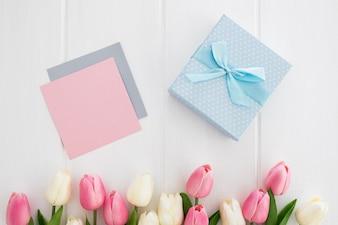 Голубой подарок с открыткой и тюльпаны на белом фоне деревянные на день матери