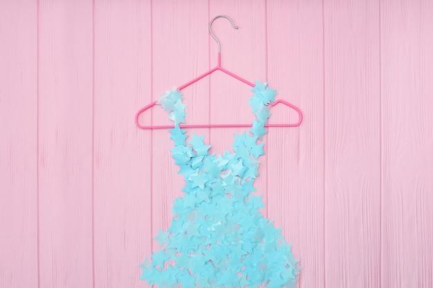 Blue girls stylized dress hanging on pink background