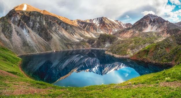 Голубое ледниковое озеро высоко в горах. атмосферный зеленый пейзаж с озером в высокогорной долине. горный алтай.