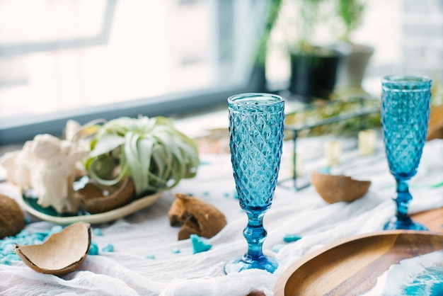 Blue glass glasses on the holiday table, broken coconuts in the table setting. tropical or marine style decor in the decoration. color of the year 2020, classic blue