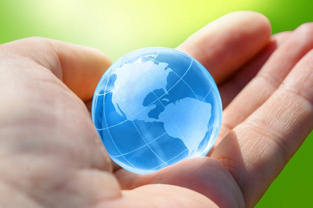 Синий стеклянный шар планеты земля в человеческой руке