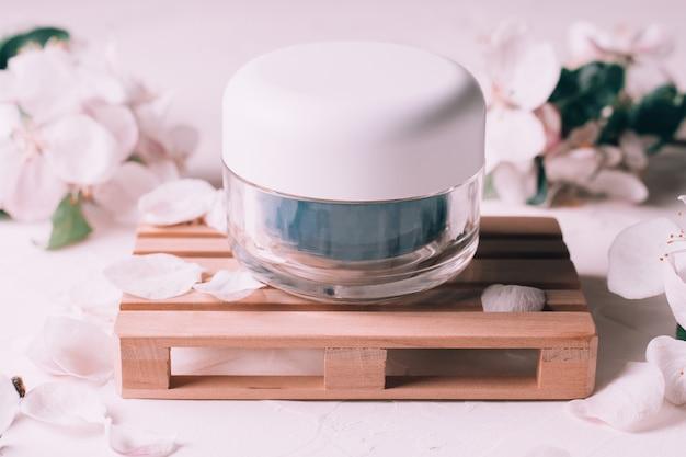 Синяя стеклянная банка крема на деревянном подиуме в виде поддона, на светлой штукатурке с цветами яблони
