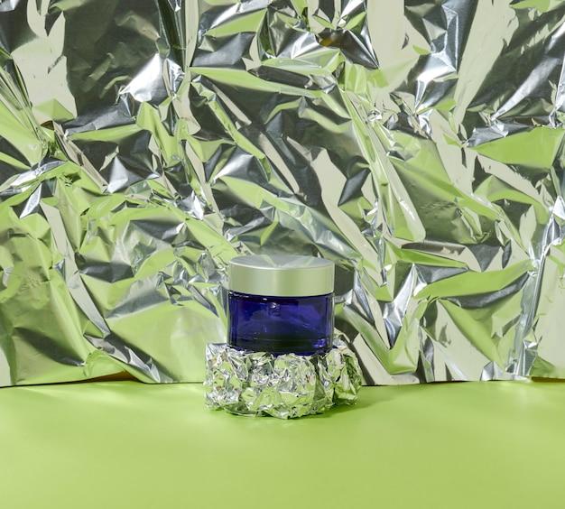 구겨진 호일이 있는 추상적 배경에 화장품용 회색 플라스틱 뚜껑이 있는 파란색 유리 항아리. 화장품 크림, 마스크, 세럼 브랜딩
