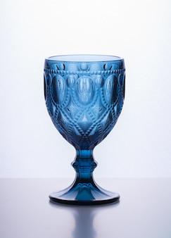 Бокал синего стекла на размытом белом фоне