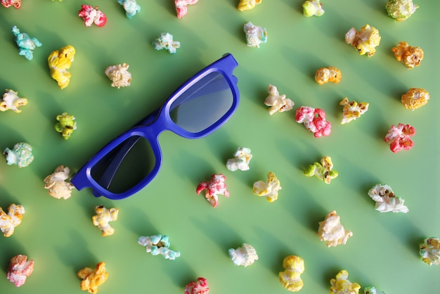Blue glasses to watch the movie in 3d among colored popcorn.