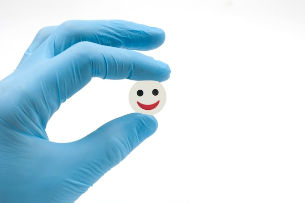 A blue gloved hand holds a tablet with its fingers a smile for all diseases on a white background