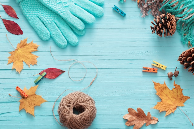 Blue gloves and autumn leaves on wooden background