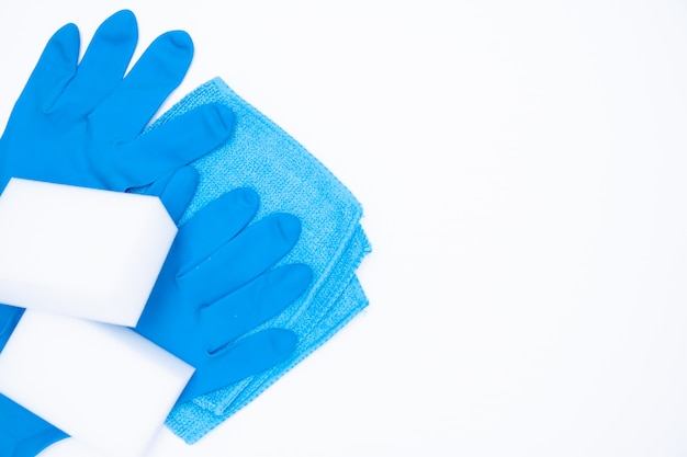 Blue gloves and rag sponge on white. cleaning set top view. flat lay