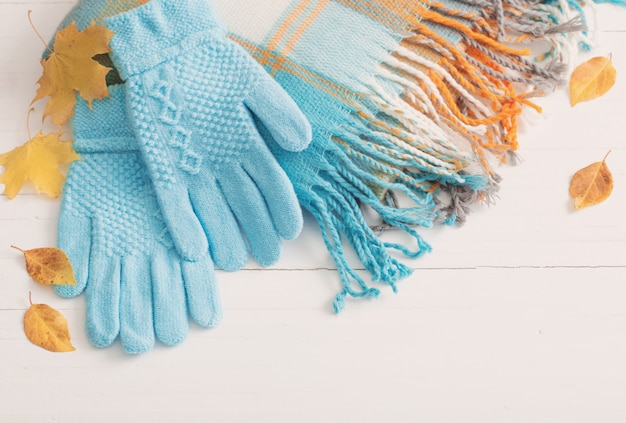Blue gloves and scarf on wooden white background