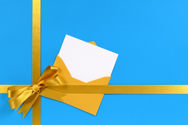 Blue and gold gift with blank invitation or greetings card.