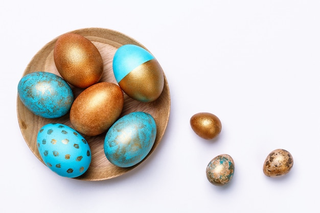 Blue and golden modern easter eggs on a wooden plate. .