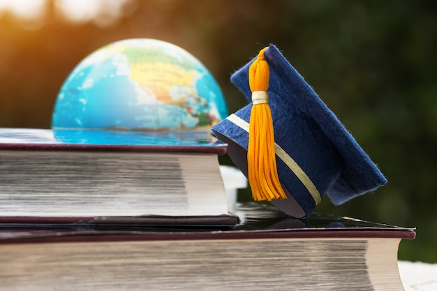 Blue graduation cap on opening textbook with blur of america earth world globe model map in library room of campus