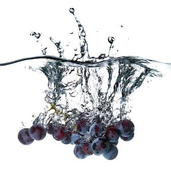 Синий виноград упал в воду с брызгами, изолированными на белом