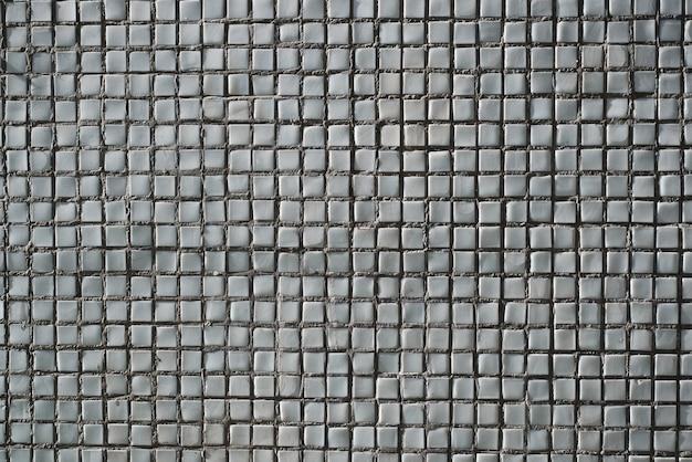 建物の外壁、壁にある青灰色の小さな正方形の装飾タイル。テクスチャの背景。