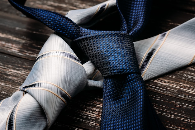 Blue and gray ties on wooden background