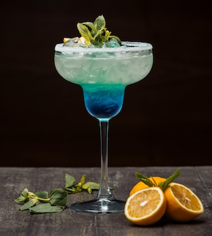Blue and green cocktail garnished with lemon and mint in long stem glass