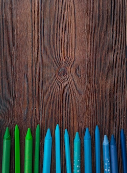 Blue and green color crayons arranged in row over wooden table