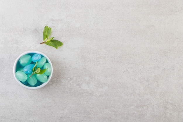 Blue and green hard candies in bowl placed on stone table.